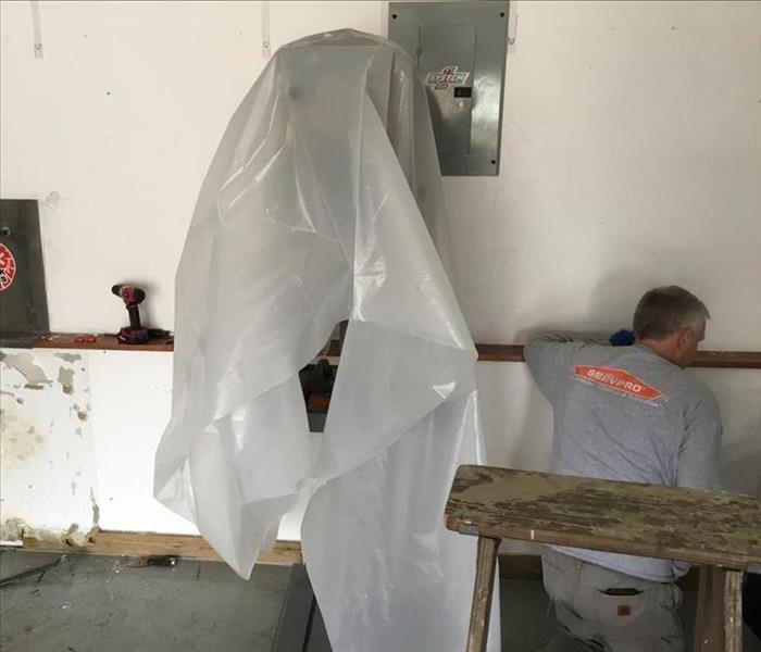 a basement wall with a SERVPRO team member removing the wall