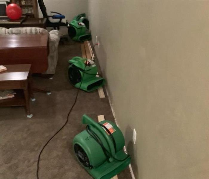 A wall with trim removed and air movers in place