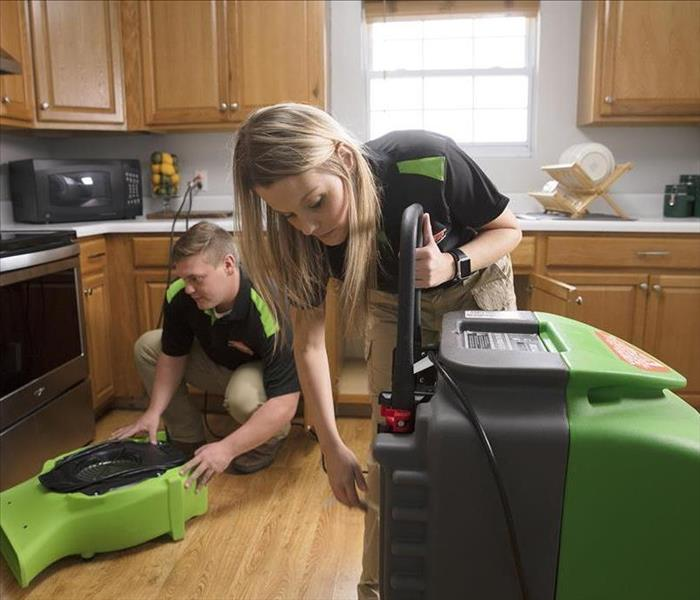 Two SERVPRO workers setting up drying equipment