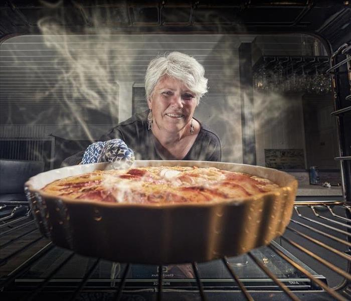 Woman pulling out apple pie from oven with steam